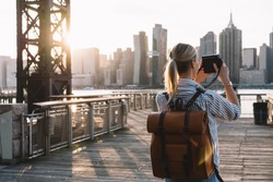 Back view of stylish female tourist with traveling backpack standing on American urban setting and clicking pictures of Manhattan landmark using retro instant camera, concept of photography hobby