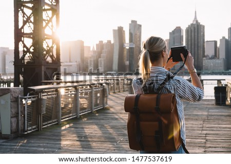Back view of stylish female tourist with traveling backpack standing on American urban setting and clicking pictures of Manhattan landmark using retro instant camera, concept of photography hobby #1477537619