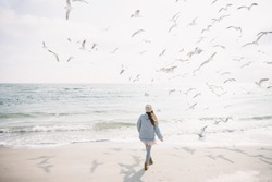 back view of stylish girl on winter seashore with seagulls