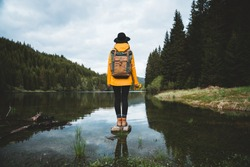 Back view of stylish hipster woman holding flowers,wearing vintage backpack, hat and yellow jacket looking at mountain view while relaxing in nature. Travel and wanderlust concept.Amazing chill moment