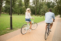 back view of stylish man and woman riding bicycles in park
