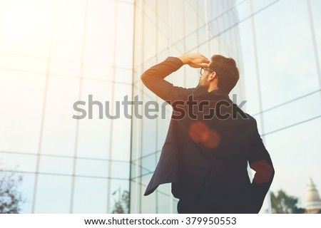 Back view of successful man entrepreneur looking up on modern skyscraper while standing outdoors, young executive male director admires something on the distance during work break outside of company #379950553