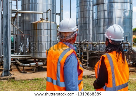 Back view of successful older business manager in discussion with employee on site at chemical plant. Diversity of ethnic background, Caucasian and African American, age and gender.Non urban. Outdoors