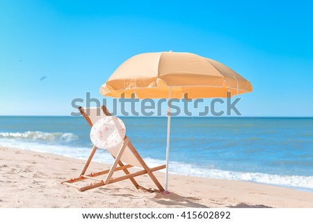 Back View Of Sun Parasol, Woman's Hat and Deckchair On Sandy Beach Vacation #415602892