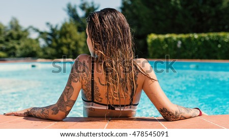 Stock Photo Back view of tattooed woman relaxing in swimming pool.