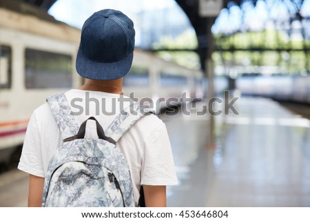 Back view of teenage school boy wearing white T-shirt and cap with a backpack on his back walking home from school. Urban background with copy space for your advertising content. Selective focus
