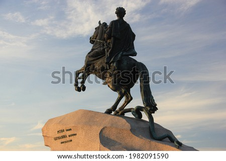 Back view of the Bronze Horseman statue of Peter the Great situated in the Senate Square in St. Petersburg in Russia, the statue in illuminated by golden sunlight, blue cloudy sky is in the background Foto stock ©
