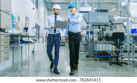 Back View of the Head of the Project Holds Laptop and Discussing Product Details with Chief Engineer while They Walk Through Modern Factory. Stockfoto ©
