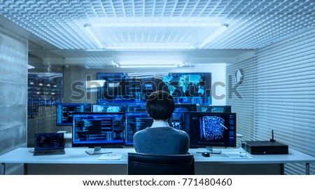 Back View of the IT Engineer Working with Multiple Monitors Showing Graphics, Functional Neural Network. He Works in a Technologically Advanced System Control Data Center.