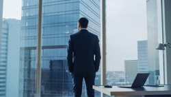 Back View of the Thoughtful Businessman wearing a Suit Standing in His Office, Hands in Pockets and Contemplating Next Big Business Deal, Looking out of the Window. Big City Business District View