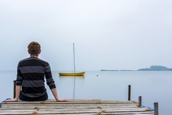 back view of thoughtful young man sitting on wooden  pier on seaside and looking into the distance on the boat in the sea. human emotions and feelings concept. thoughtful, longing and loneliness