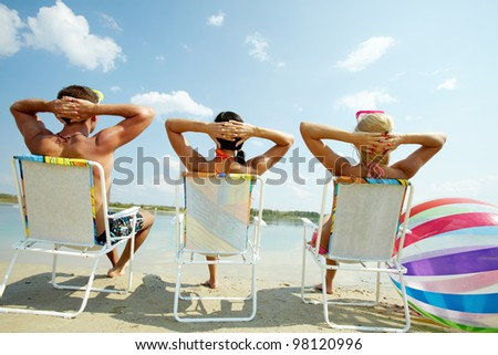 Back view of three friends resting in chairs on the beach