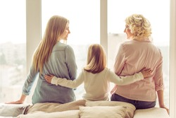 Back view of three generations of beautiful women sitting on sofa against window