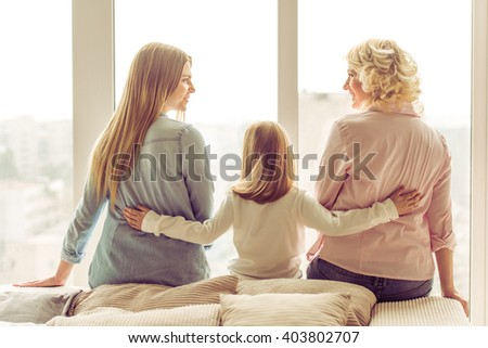 Back view of three generations of beautiful women sitting on sofa against window #403802707