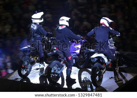 Back view of three motorcross racers in helmets on stage #1329847481