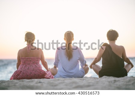 Shutterstock Back view of three woman sitting at the beach and meditate