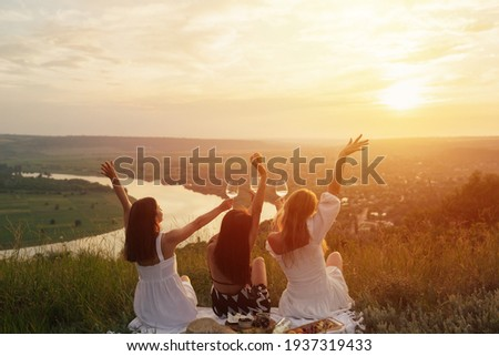 Back view of three young female friends is having picnic with wine, cheese and fresh fruits on hill at sunset.