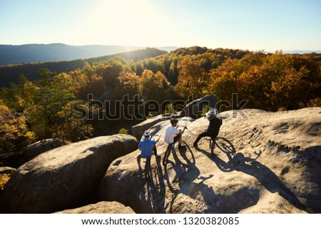Back view of three young sportsmen with trial bicycles having a rest on the big boulder on the top of mountain. Guys enjoying beautiful view of setting sun and forest. Concept of extreme sport
