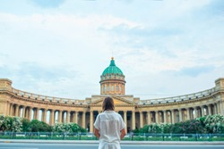 Back view of tourist girl looking at Kazan Cathedral in Saint Petersburg. One of most famous churches and museums of Russia. Beautiful architecture of Petersburg.