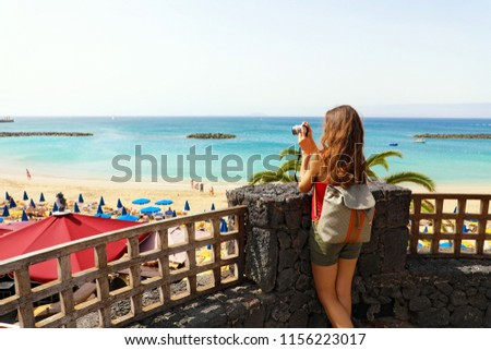 Back view of traveler girl taking picture from terrace of Playa Dorada seascape, Lanzarote, Canary Islands