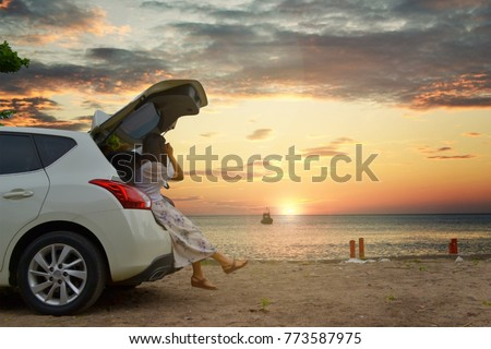 Back view of traveler young woman taking a photo of beautiful sunset while sitting on hatchback car against the copy space sea, clouds and sky background