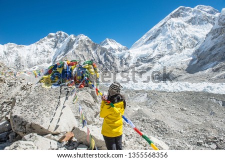 Back view of trekker woman praying and respect to the memorial in Everest Base Camp (5,380 m) the place are used by mountain climbers during their ascent and descent to Mt.Everest, Nepal. #1355568356