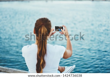 Back view of trendy female holding mobile phone in hands looking at cellphone camera and taking image of herself, caucasian hipster girl sitting outdoors and using smartphone clicking selfie photo #1424736038