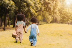 Back view of two adorable african children, girl and boy holding hand and walking together in garden. Happy little dark skinned two kids walking on grass in park and outdoor. Happy family concept.