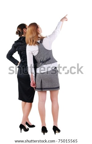 Back view of two beautiful young business woman looking at wall. Rear view. Isolated over white.