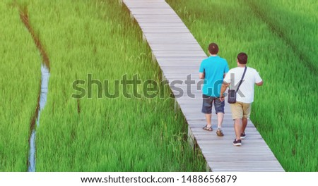 Back view of two male friends walk and take photography along the bamboo path that crossed through the fields in the evening before the sun set down on the horizon. #1488656879