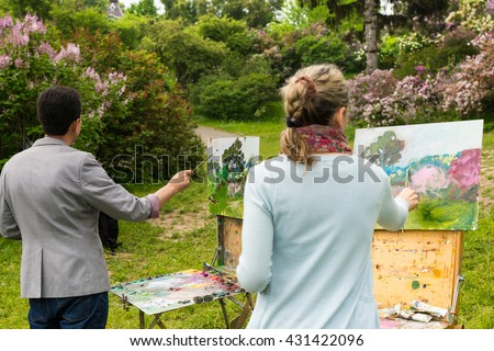 Back view of two professional painters standing in front of their easels and painting outdoors with background of beautiful trees