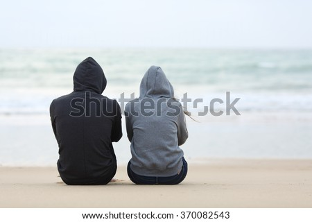 Stock Photo Back view of two sad teenagers sitting on the sand of the beach and looking at horizon in a bad weather day