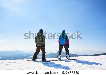 Back view of two tourists snowboarders in sportive equipment standing on snowboards on copy space background of blue sky and woody mountains on sunny winter day. Extreme winter sports concept. #1522653650