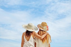 Back view of two woman relax on holiday.Lesbian Couple in white clothes near sea.  Two cute girl against blue sky with clouds.
