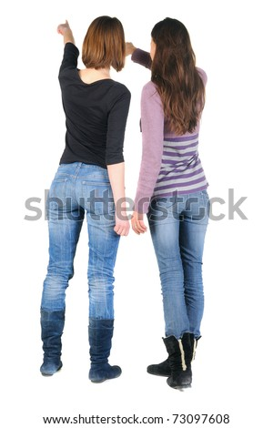 Back view of two women pointing at wall. Rear view. Isolated over white.