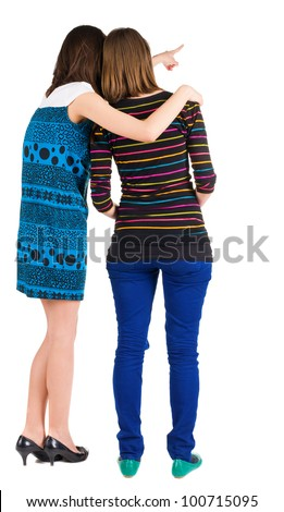 Back view of two young  brunette woman pointing at wall . Rear view people collection.  backside view of person.beautiful girl friends  showing gesture.   Isolated over white background.