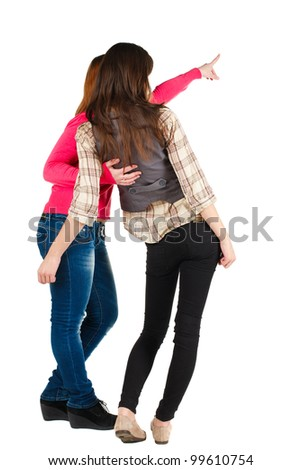 Back view of two young woman (brunette and blonde) pointing at wall . beautiful girl friends  showing gesture. Rear view. Isolated over white background.
