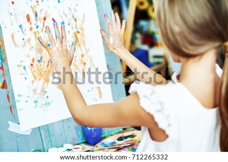 Back view of unrecognizable little girl standing at easel and doing finger-painting, her hands covered with watercolors