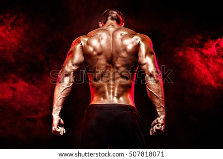 Back view of Unrecognizable man, strong muscles posing with arms down in smoke.