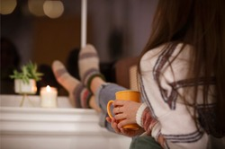 Back view of unrecognizable woman in warm clothes enjoying hot beverage and relaxing in cozy room in evening at home