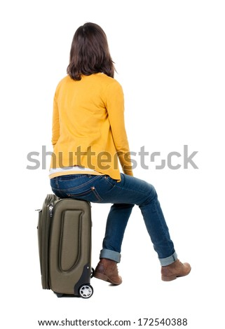 Back View Of Walking Woman In Cardigan Sits On A Suitcase