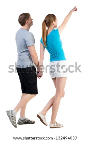 Back view of walking young couple (man and woman) pointing. curious wife shows her husband attractions. Rear view people collection. backside view of person. Isolated over white background