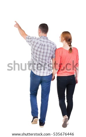 Back view of walking young couple (man and woman) pointing. Rear view people collection. backside view of person. Isolated over white background #535676446