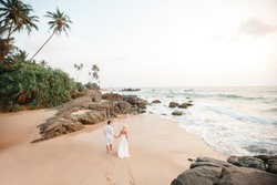 Back view of wedding couple is running on the sea beach. Sunny summer photo. Bride with groom on tropical beach . Romantic ceremony on the beach
