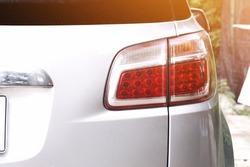 Back view of white car. White car and taillight. White car parked in the parking lot. White car for transportation.