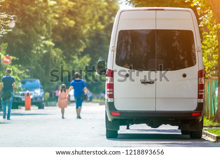 Back view of white passenger medium size commercial luxury minibus van parked n shadow of green tree on summer city street i with blurred silhouettes of pedestrians and cars under green trees. #1218893656