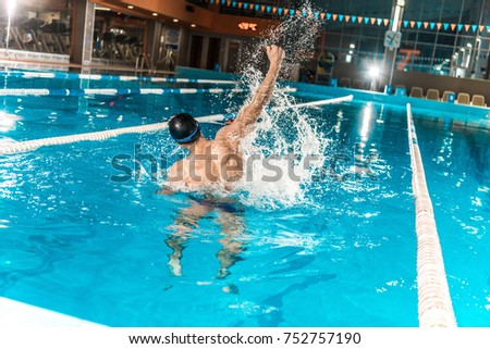 back view of winning swimmer gesturing in competition swimming pool  #752757190
