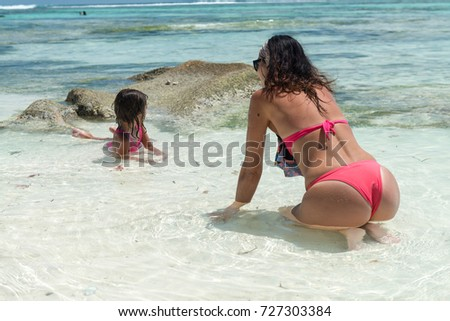 Back view of woman and daughter relaxing in the sea water.