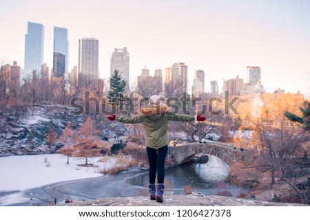 Back view of woman enjoy the view of ice-rink in Central Park and skyscrapers on Manhattan in New York City