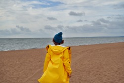 Back view of woman in bright yellow cloak and red hat on shore of North sea on cold autumn day. Mood Scandinavian weather, deserted beach